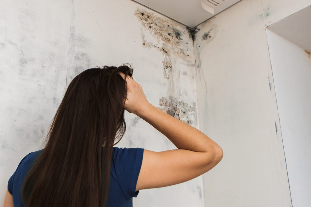 Woman looking worried at wall with mold